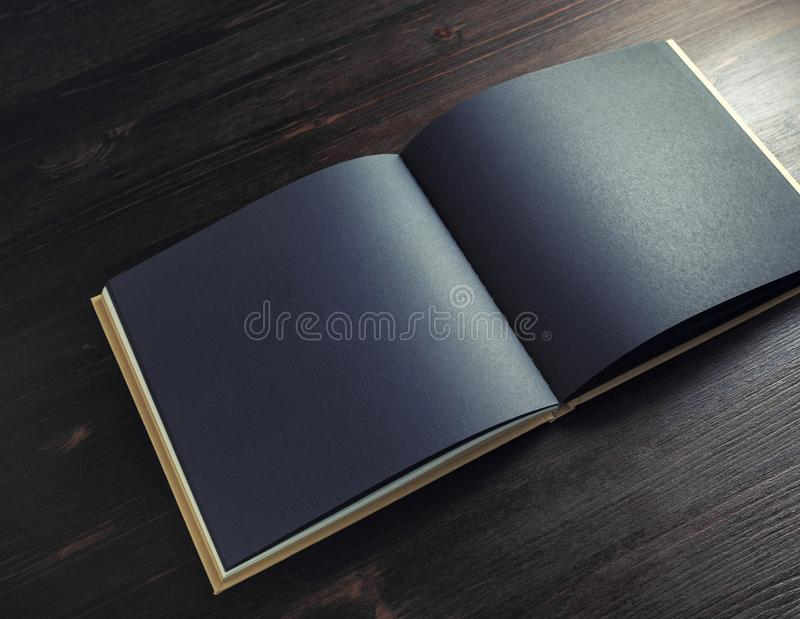 Black brochure mock up. Photo of blank black brochure mock up on dark wood table background. Copy space for text stock photos