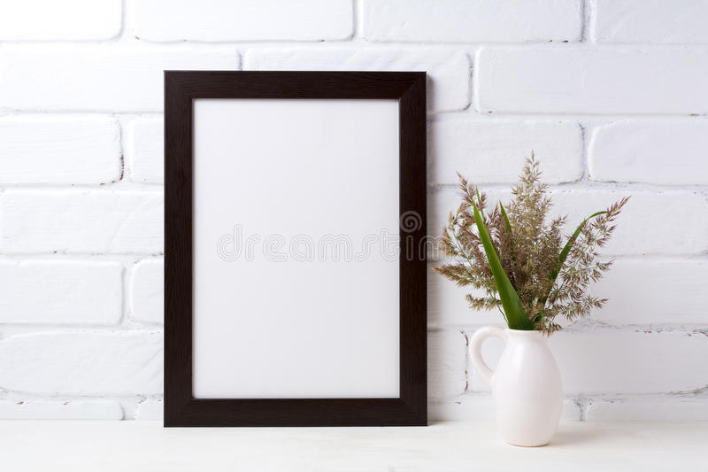 Black brown frame mockup with grass and green leaves in pitcher. Black brown frame mockup with meadow grass and green leaves in pitcher vase near painted brick royalty free stock photos