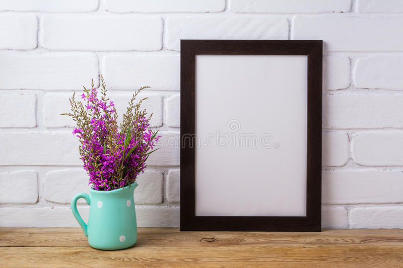 Black brown frame mockup with maroon purple flowers in mint pit stock image
