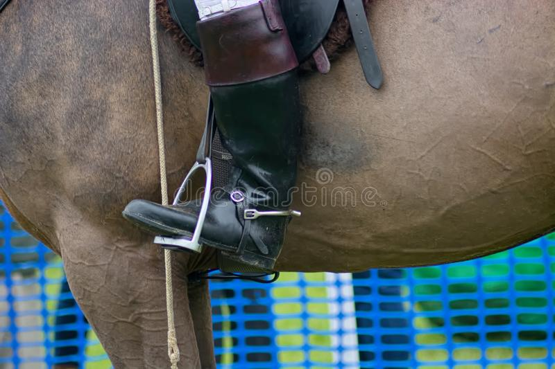 Black & brown leather riding boots in stirrup. Leather Riding boots of the huntsman, with foot in stirrup on boards his horse royalty free stock photography