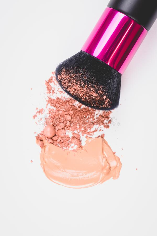 Black brush for make up and crushed texture of beige face powder and beige makeup smear of creamy foundation on isolated backgound.  royalty free stock photos