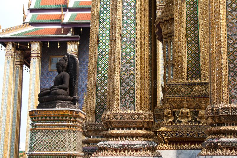 Black buddha statue and columns pattern detail. In Wat Phra Kaew temple within Grand Palace complex in Bangkok, Thailand stock photography