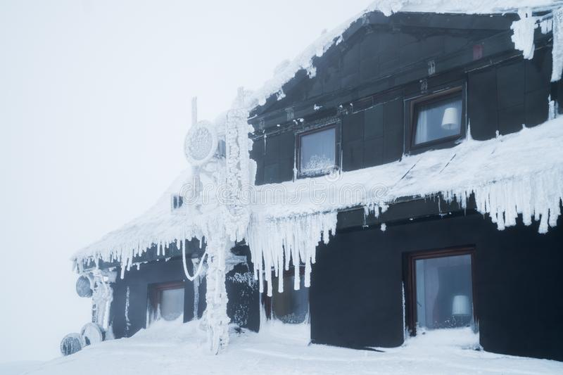 Black building in mountains covered with snow and ice, during very cold day in winter stock photography