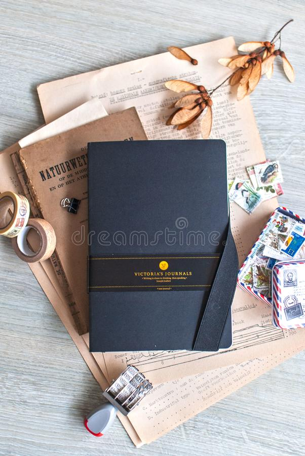 A black bullet journal lying on wooden surface and surrounded by real vintage or vintage looking stuff. Bullet journal trend. stock photography