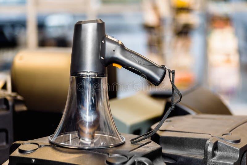 Black bullhorn public address megaphone on a loudspeaker. In a blurry background royalty free stock photos