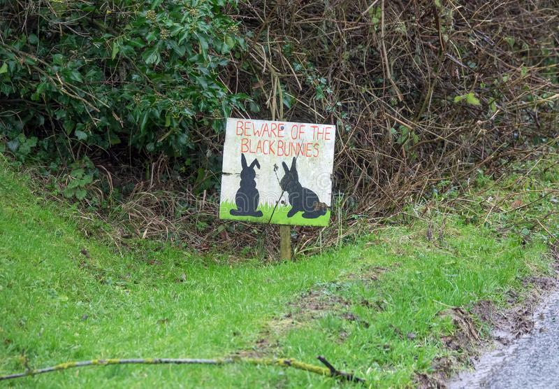 Black Bunny Sign and Verge. Sign on grass verge by road in Milton Street, East Sussex, warning drivers to watch out for black rabbits royalty free stock image