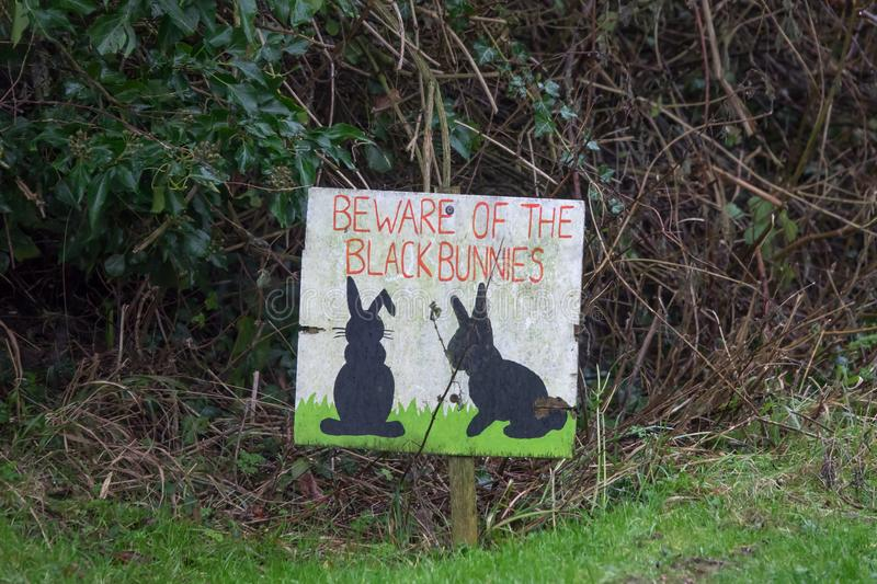 Black Bunny Sign Warning Beware. Sign on grass verge by road in Milton Street, East Sussex, warning drivers to watch out for black rabbits royalty free stock photography