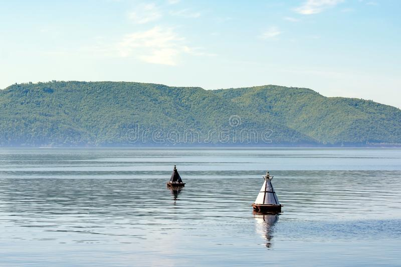 Black buoy and white buoy on the mountain background stock photo
