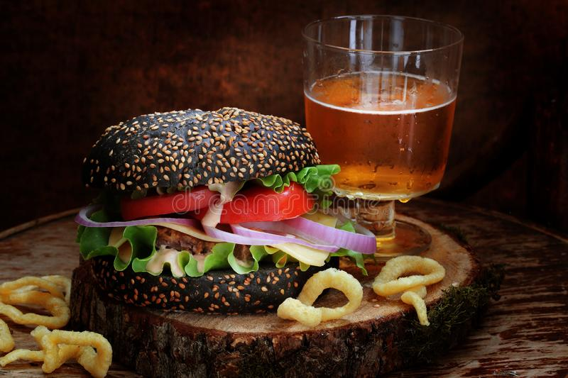 Black burger with beer and onion rings. On a wooden table royalty free stock photos