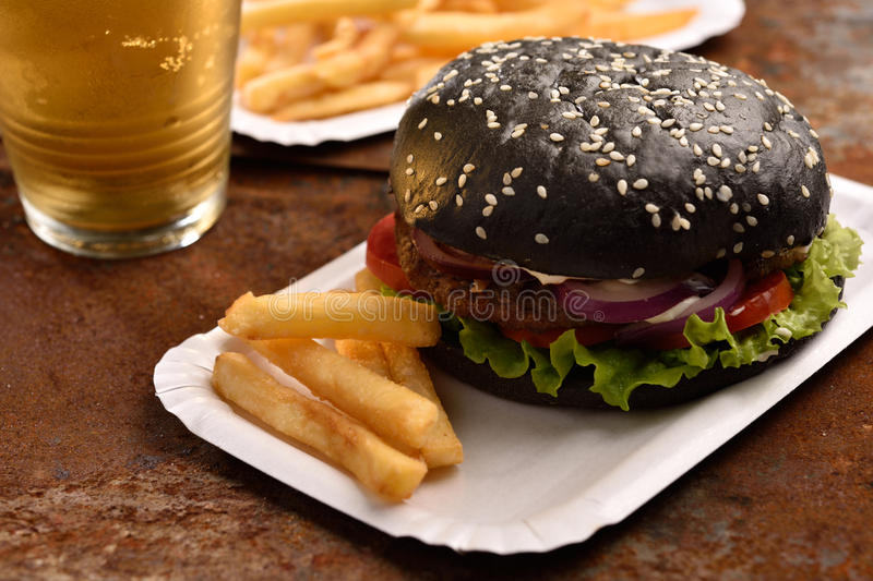 Black burger with French fries royalty free stock photos