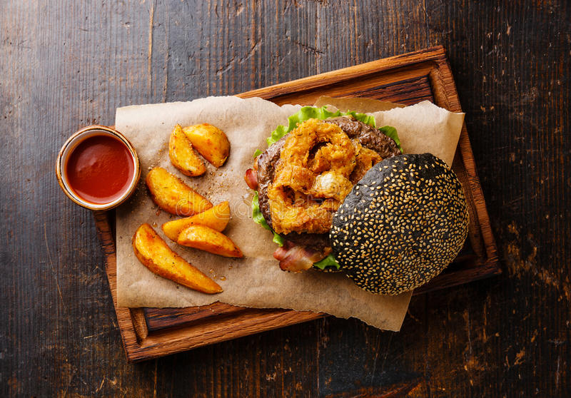 Black burger with meat, onion rings fries and potato wedges. Black burger with sesame seed bun, meat, bacon, onion rings fries and potato wedges on dark wooden royalty free stock images