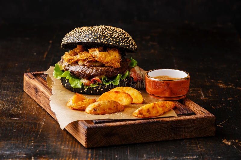Black burger with meat, onion rings fries and potato wedges. Black burger with sesame seed bun, meat, bacon, onion fries rings and potato wedges on dark wooden royalty free stock photos