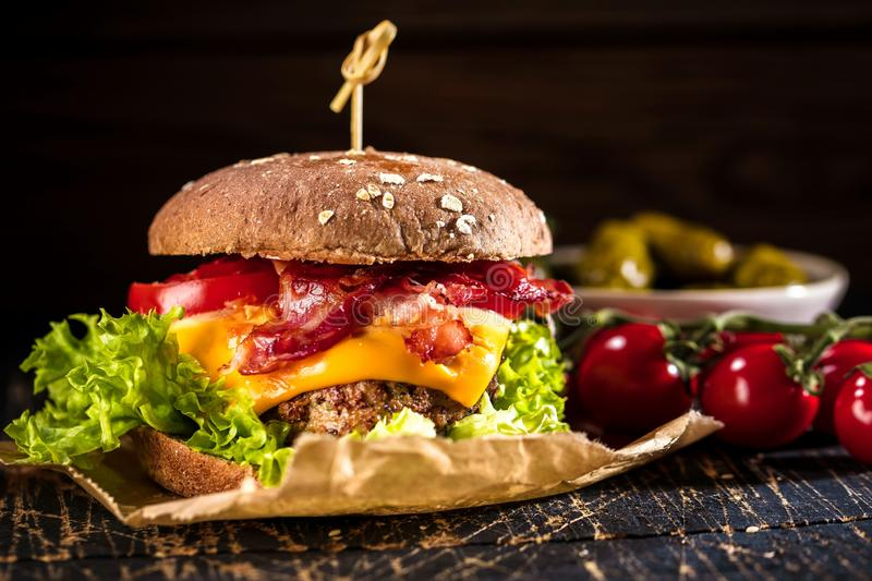 Black burger with meat patty, cheese, tomatoes, mayonnaise. Dark wooden rustic table. Modern fast food lunch.  stock photography