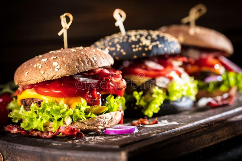 Black burger with meat patty, cheese, tomatoes, mayonnaise. Dark wooden rustic table. Modern fast food lunch.  royalty free stock images