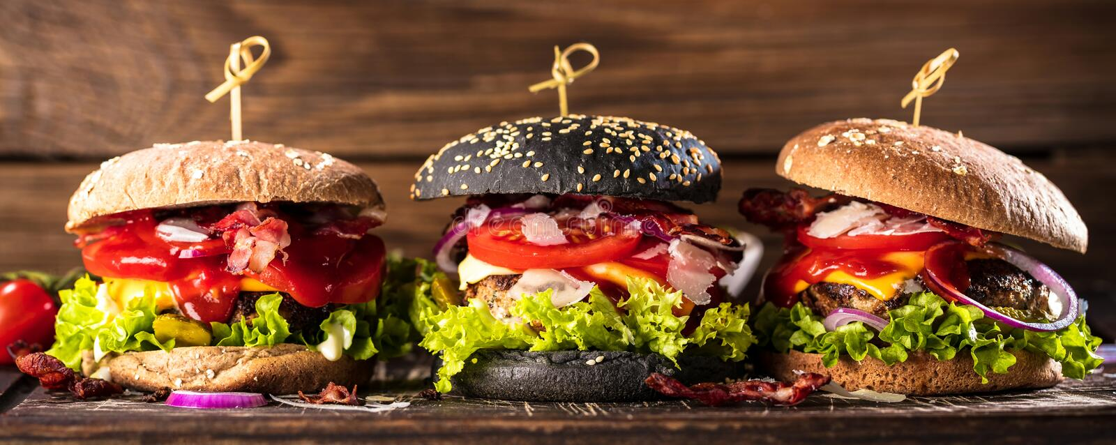 Black burger with meat patty, cheese, tomatoes, mayonnaise. Dark wooden rustic table. Modern fast food lunch.  royalty free stock photography