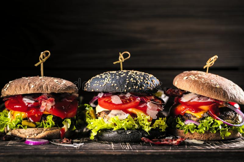 Black burger with meat patty, cheese, tomatoes, mayonnaise. Dark wooden rustic table. Modern fast food lunch.  royalty free stock photo
