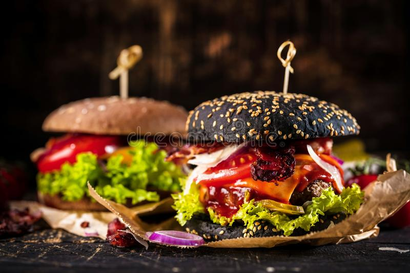 Black burger with meat patty, cheese, tomatoes, mayonnaise. Dark wooden rustic table. Modern fast food lunch.  stock photo