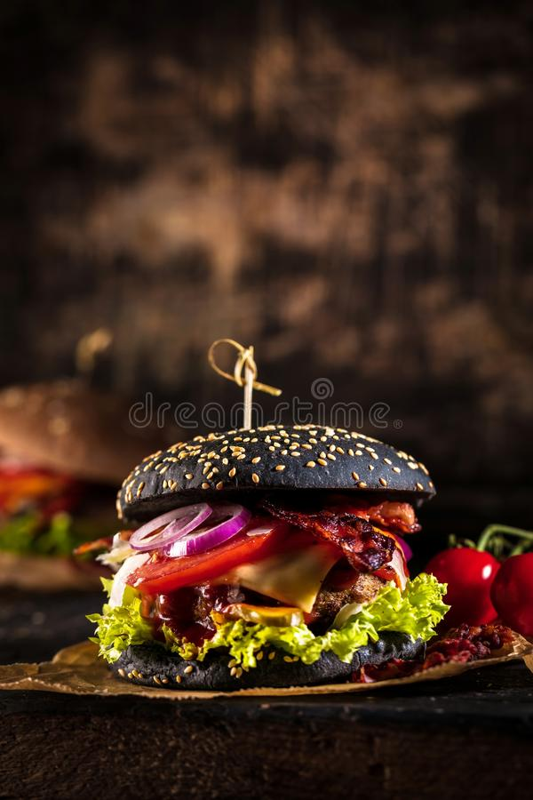 Black burger with meat patty, cheese, tomatoes, mayonnaise. Dark wooden rustic table. Modern fast food lunch.  stock image