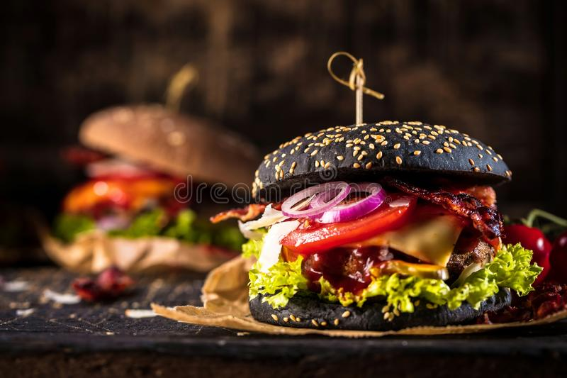 Black burger with meat patty, cheese, tomatoes, mayonnaise. Dark wooden rustic table. Modern fast food lunch.  royalty free stock image