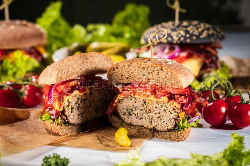 Black burger with meat patty, cheese, tomatoes, mayonnaise. Dark wooden rustic table. Modern fast food lunch.  royalty free stock photos