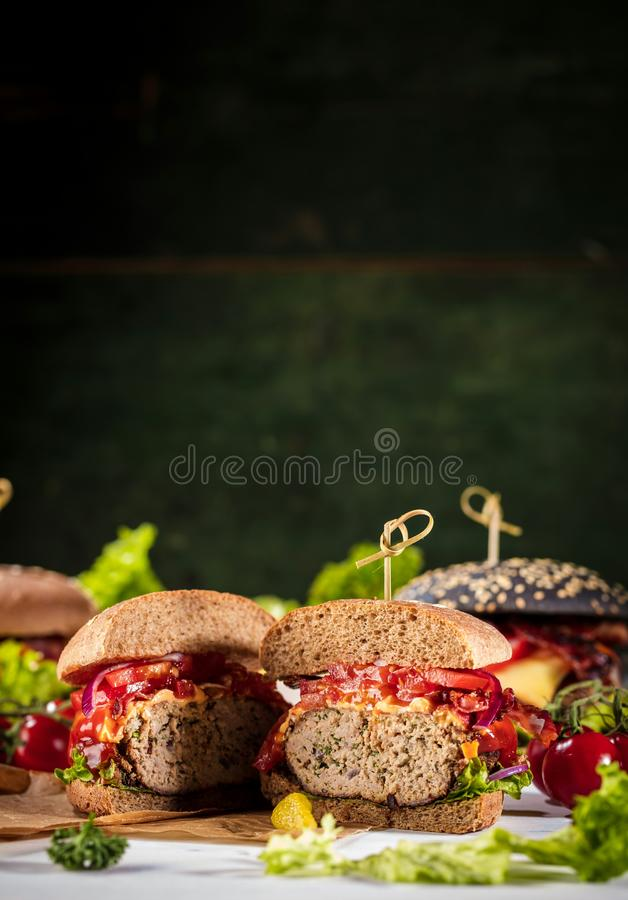 Black burger with meat patty, cheese, tomatoes, mayonnaise. Dark wooden rustic table. Modern fast food lunch.  stock photos