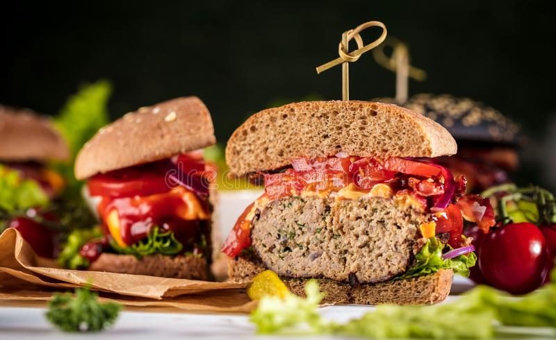 Black burger with meat patty, cheese, tomatoes, mayonnaise. Dark wooden rustic table. Modern fast food lunch.  stock images