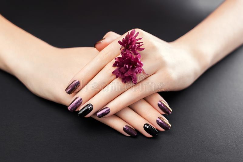 Black and burgundy manicure with flowers on black background. Gel nail polish with mirror powder pigment. Body care stock photos