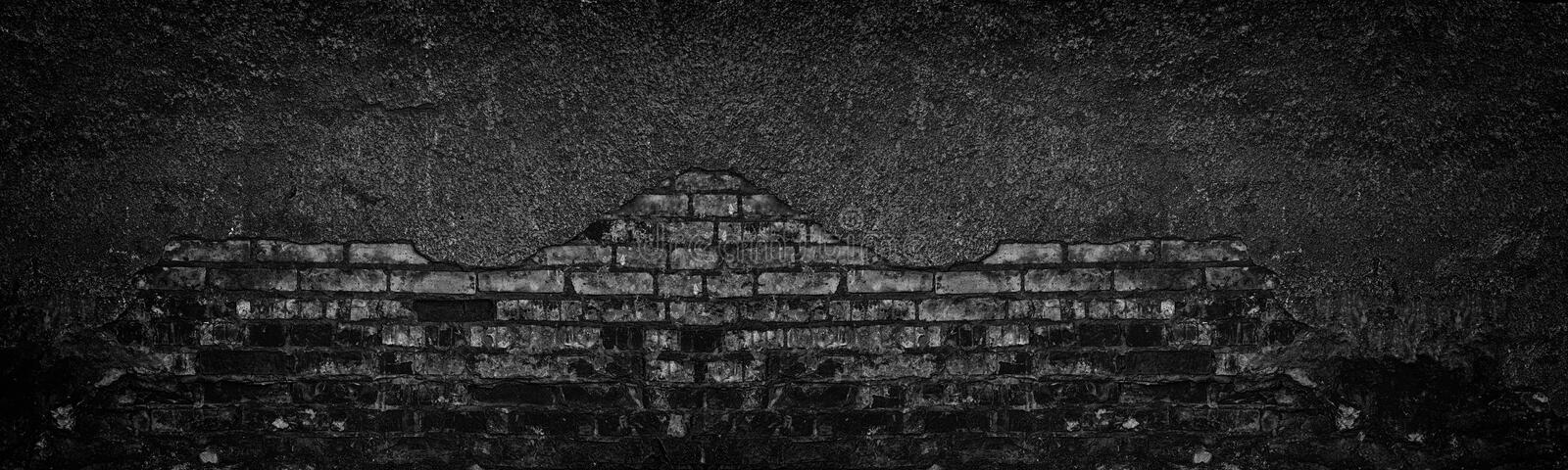 Black burnt brick wall with fallen off plaster wide texture. Crumbled old shabby brickwork. Dark gloomy background. Black burnt brick wall with fallen off stock photo