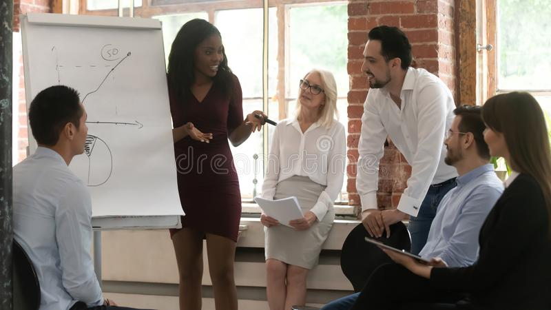 Black business woman coach training team giving flip chart presentation. Black business women manager coach training sales team giving flip chart presentation stock image