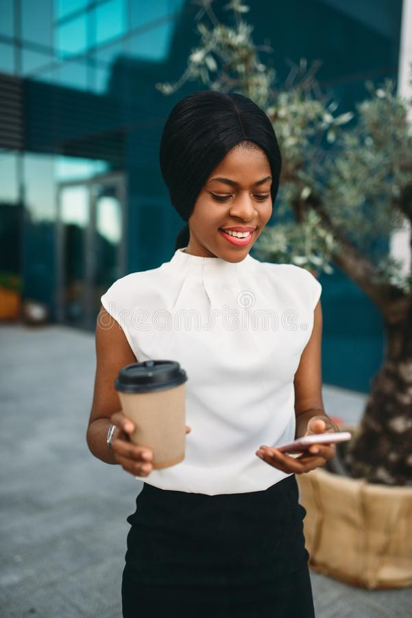 Black business woman with coffee uses mobile phone stock photo