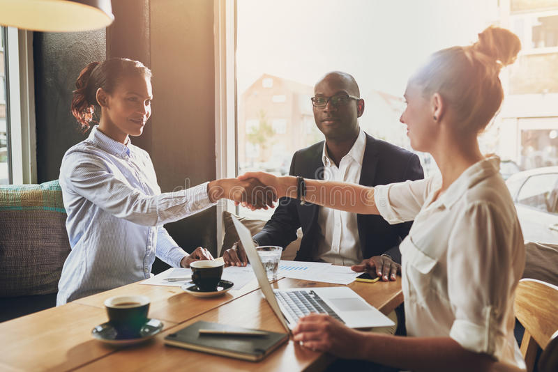Black business woman and white business woman shaking hands stock image