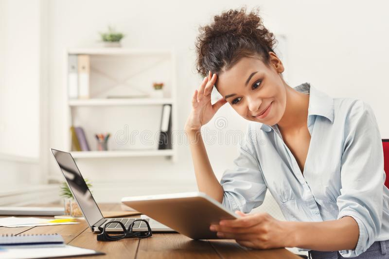 Black business woman working on digital tablet. Smiling young african-american business woman in formalwear working on digital tablet, sitting at office, copy royalty free stock photography