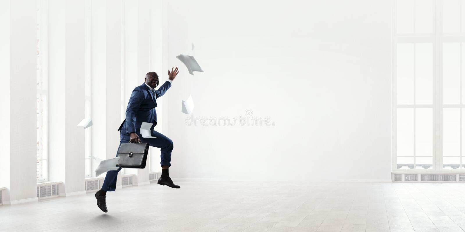 Black businessman with briefcase running among flying papers indoor royalty free stock photography