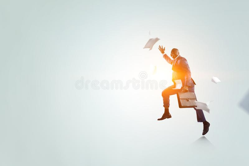 Black businessman with briefcase running among flying papers with sunshine on white background stock images