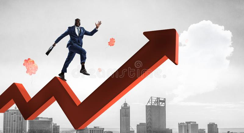 Black businessman climbing red zigzag increasing arrow. Black happy businessman climbing red zigzag rising arrow surrounded by red flying bitcoin balloons royalty free stock photo