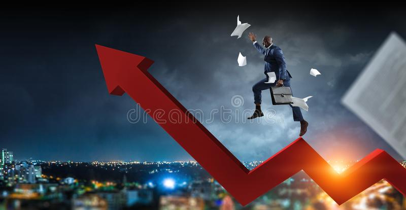 Black businessman climbing on red zigzag increasing arrow surrounded by flying papers on a dark storm cloudy cityscape royalty free stock photos