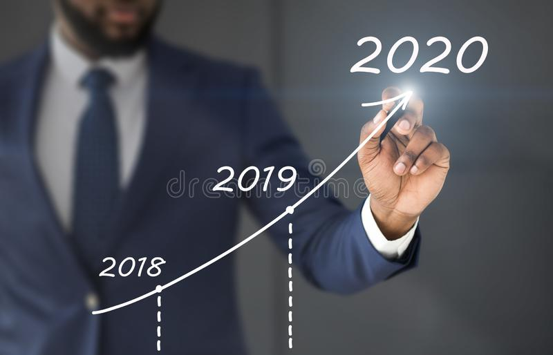 Black businessman drawing rising diagram with business strategy up to 2020 royalty free stock image