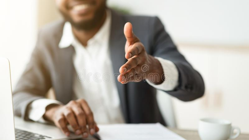 Black businessman gives hand for handshake proposes partnership royalty free stock photo