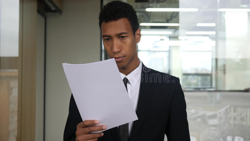 Black Businessman Reading Documents in Office royalty free stock photos