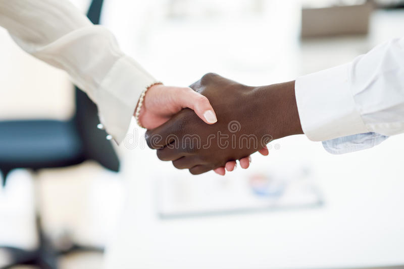 Black businessman shaking hands with a caucasian businesswoman stock photo