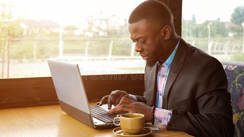 Black businessman is working typing a message on laptop sitting in summer cafe. Afro american businessman is typing a message on laptop sitting in summer cafe royalty free stock photography
