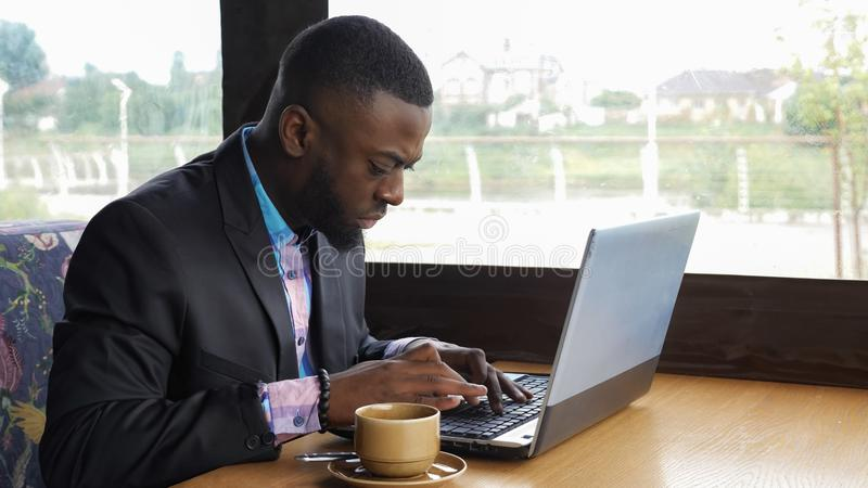 Black businessman is working typing a message on laptop sitting in summer cafe. Afro american businessman is typing a message on laptop sitting in summer cafe royalty free stock image