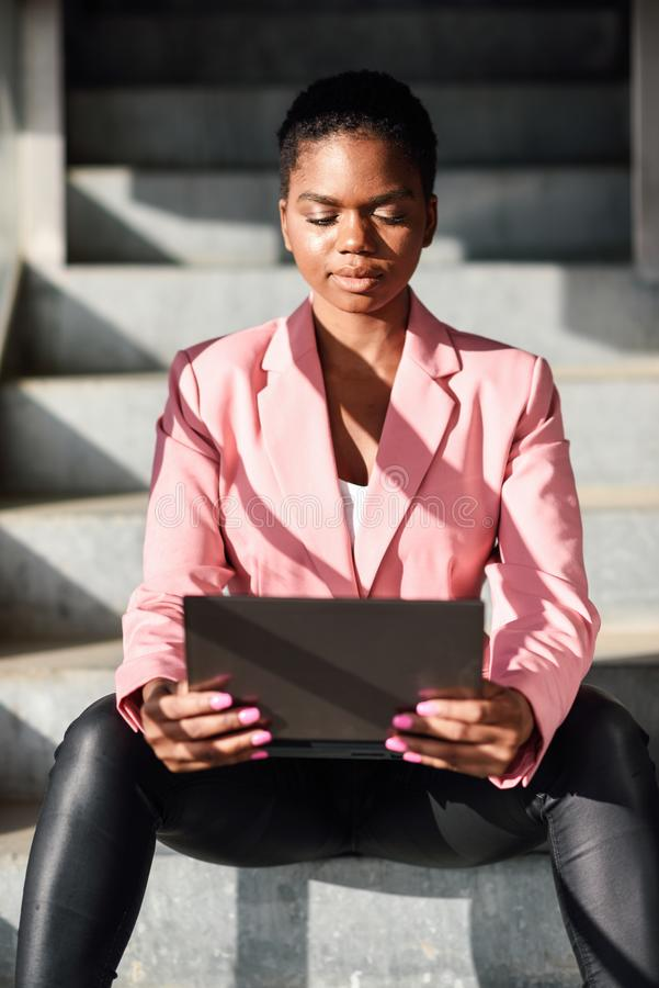 Black businesswoman sitting on urban steps working with a laptop computer. stock photography