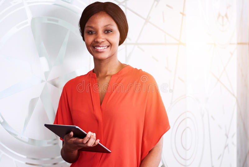 Black businesswoman smiling at camera while holding electronic tablet. Black businesswoman smiling at camera while holding an electronic tablet in one hand and stock images