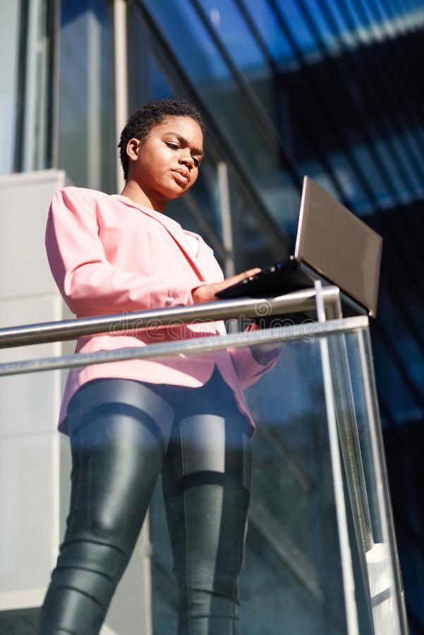Black businesswoman standing near business office building working with a laptop computer. stock photos