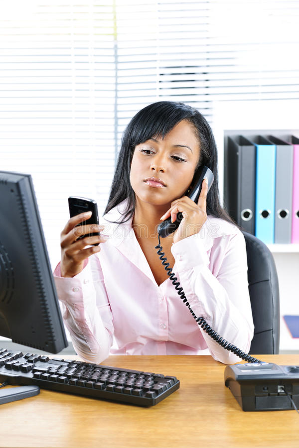 Black businesswoman using two phones at desk royalty free stock photo