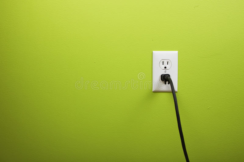 Black Cable Plugged In A White Electric Outlet Royalty Free Stock Image