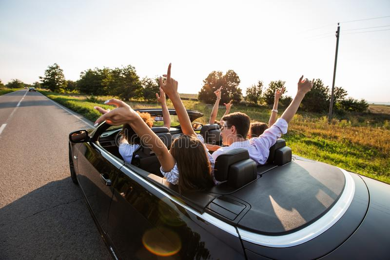 Black cabriolet is on the country road. Happy group of young girls and guys are sitting in the car hold their hands up royalty free stock image