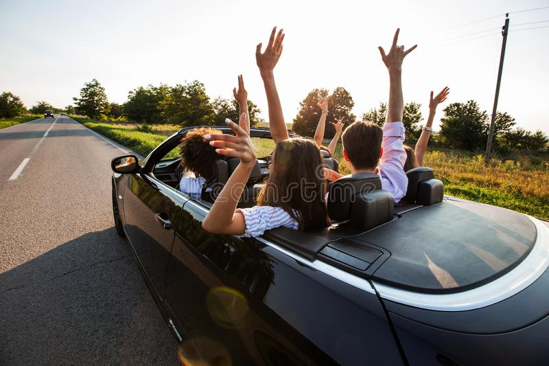Black cabriolet is on the country road. Happy group of young girls and guys are sitting in the car hold their hands up stock image