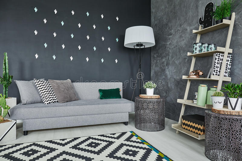 Black cactus wall decor. Room with black cactus wall decor and sofa royalty free stock images